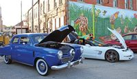 Robinson's newest mural serves as a backdrop for entries in the the annual Heath Harvest Festival car show Friday, including a bullet-nose Studebaker. Crawford County Collectibles sponsored the show. The group's next event is a Halloween-themed show at Dog n' Suds Oct. 15. Randy Harrison | Daily News