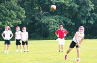 Lawrenceville quarterback Brenyn Winningham fires a pass, while coach Travis Reider and teammates Hayden Frey, Luke Hatfield and Wyatt Bice look on in the background during Saturday's 7-on-7 event at Robinson. The Indians went 3-2 on the day and finished seventh out of 16 teams. Tom Osborne | Daily Record