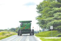 A reflective orange triangle bordered in red marks slow moving vehicles, such as combines and tractors. Drivers should slow down when driving behind large machinery and pass only when it is safe and legal to do so. Contributed photo